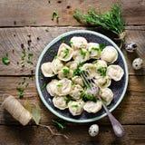 Pelmeni russo tradizionale, ravioli, gnocchi con carne sulla tavola di legno con farina, prezzemolo, uova di quaglia, pepe Immagini Stock