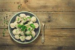 Pelmeni russo tradizionale, ravioli, gnocchi con carne sulla tavola di legno con farina, prezzemolo, uova di quaglia, pepe Fotografia Stock
