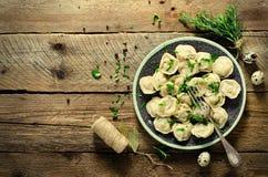 Pelmeni russo tradizionale, ravioli, gnocchi con carne sulla tavola di legno con farina, prezzemolo, uova di quaglia, pepe Fotografie Stock