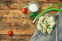 Pelmeni with spicy herbs, sour cream, cherry tomatoes. Napkin canvas on wooden table, traditional russian cuisine, rustic style Stock Images