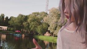Pelo atractivo de la caricia de la chica joven cerca de la charca en el parque del amusment almacen de metraje de vídeo