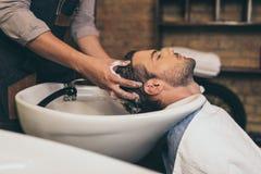 Pelo cosechado de los clientes del peluquero de la visión que se lava en peluquero Fotografía de archivo