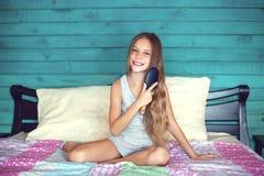 Pelo de cepillado de la muchacha en dormitorio Imágenes de archivo libres de regalías