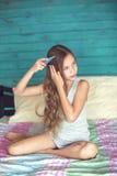 Pelo de cepillado de la muchacha en dormitorio Imagenes de archivo