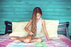 Pelo de cepillado de la muchacha en dormitorio Foto de archivo libre de regalías