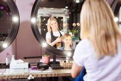 Pelo de cepillado del peluquero encantador de su cliente Foto de archivo libre de regalías