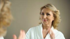 Pelo de cepillado de la mujer mayor atractiva en espejo delantero y la sonrisa, belleza envejecida metrajes