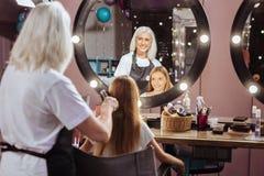 Pelo de cepillado de las muchachas del peluquero mayor alegre Foto de archivo