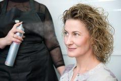 Pelo de la mujer de la fijación del peluquero con la laca de pelo Foto de archivo libre de regalías