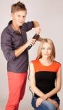 Pelo de la mujer del estilista que plancha en salón del peluquero Imagen de archivo