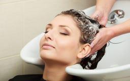 Pelo de la mujer del peluquero que se lava. Salón de belleza de la peluquería Foto de archivo libre de regalías