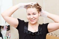 Pelo de la mujer que teñe en el cuarto de baño Fotografía de archivo