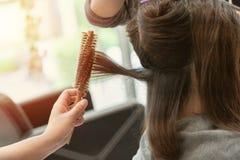 Pelo de los woman's el hacer el brushing y del rollo imagenes de archivo