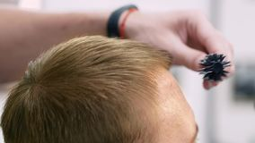 Pelo de sequía del ` s de los hombres con un secador de pelo en un salón metrajes
