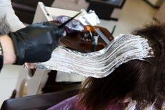 Pelo de teñido del peluquero profesional de su cliente foto de archivo