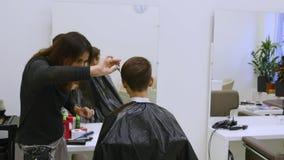 Pelo del corte de la mujer joven en el peluquero El peluquero corta el pelo a una chica joven con las tijeras profesionales almacen de metraje de vídeo