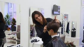 Pelo del corte de la mujer joven en el peluquero El peluquero corta el pelo a una chica joven con las tijeras profesionales metrajes