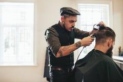 Pelo del corte del peluquero del cliente en la peluquería de caballeros imagen de archivo