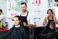 Pelo del corte del peluquero del cliente femenino Imagen de archivo libre de regalías