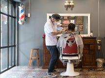 Pelo del corte del peluquero en una peluquería de caballeros Imagen de archivo