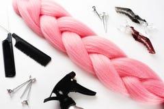 Pelo del rosa de Kanekalon rosa claro en los clips cercanos blancos de la opinión superior del fondo un peine y el espray foto de archivo libre de regalías