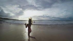Pelo del ` s de la muchacha que agita en el viento en la puesta del sol en una playa hermosa en la cámara lenta almacen de metraje de vídeo