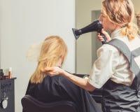 Pelo del ` s de la mujer del brushing del cosmetólogo en el salón de belleza Fotos de archivo libres de regalías