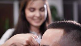Pelo femenino del ajuste del peluquero con las podadoras eléctricas Cliente masculino Foco selectivo y cierre encima de la visión almacen de video