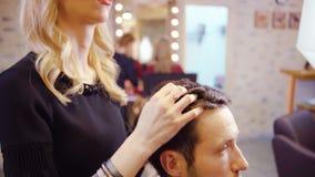 Pelo femenino del corte del peluquero del cliente del hombre en el salón de belleza almacen de metraje de vídeo