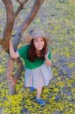 Pelo largo de la mujer hermosa con las flores amarillas en el jardín Imagen de archivo libre de regalías