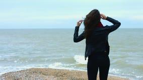 Pelo moreno conmovedor de la mujer joven que mueve encendido el viento durante caminar en la playa arenosa almacen de video