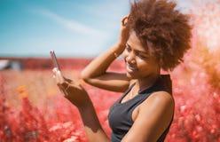 Pelo negro de la fijación de la muchacha usando la leva de su smartphone Fotos de archivo libres de regalías
