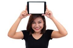 Pelo negro de la mujer asiática joven que sostiene la tableta en la cabeza Mujer que usa la tableta digital de la pantalla en bla Imágenes de archivo libres de regalías
