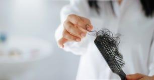 Pelo perdidoso de la mujer en cepillo para el pelo a disposición, foco suave foto de archivo