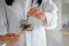 Pelo perdidoso de la mujer en cepillo para el pelo a disposición, foco suave fotos de archivo libres de regalías