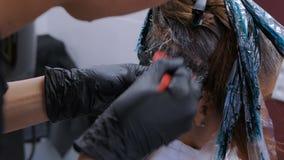 Pelo profesional del colorante del peluquero del cliente de la mujer en el estudio almacen de metraje de vídeo