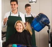 Pelo profesional del corte del estilista del blonde mayor en hairdress Imágenes de archivo libres de regalías