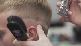 Pelo profesional del corte del peluquero con las podadoras de pelo Corte de pelo con la maquinilla de afeitar almacen de metraje de vídeo