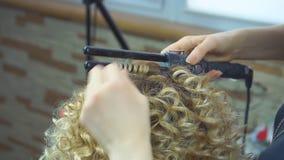 Pelo que se encrespa del estilista para la mujer blondy Cuidado de la muchacha sobre su peinado El peluquero hace rizos africanos metrajes