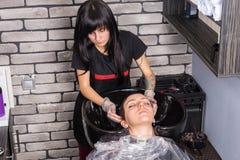 Pelo que se lava del estilista joven del cliente femenino con el pelo teñido en wa Fotografía de archivo libre de regalías