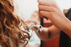 Pelo rizado, mujer con el pelo ondulado rubio largo que lo plancha, usando el hierro que se encrespa, bigudí para los rizos perfe foto de archivo