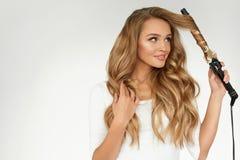 Pelo rizado Mujer hermosa que encrespa el pelo ondulado largo con hierro imagenes de archivo