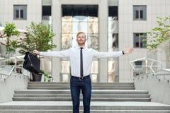 Pelo rojo adulto joven y hombre de negocios barbudo que mantienen los brazos aumentados y que expresan positividad mientras que s Imagen de archivo libre de regalías
