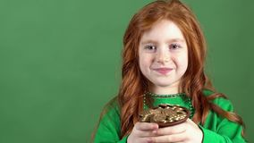 Pelo rojo de la muchacha que celebra el fondo de la pared del verde del día del ` s de St Patrick que sostiene el pote afortunado almacen de video