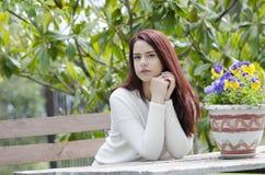 Pelo rojo lindo que se sienta en una tabla de madera del jardín Imagen de archivo libre de regalías