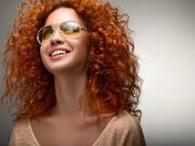 Pelo rojo. Mujer hermosa con el pelo largo rizado y Sunglases fotografía de archivo