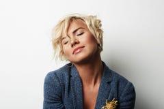 Pelo rubio hermoso de la mujer joven del retrato que lleva el fondo blanco vacío de la chaqueta azul Foto de la gente de la moda  Fotografía de archivo libre de regalías
