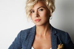 Pelo rubio hermoso de la mujer joven del retrato que lleva el fondo blanco vacío de la chaqueta azul Foto de la gente de la moda  Imagen de archivo