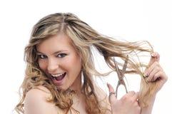 Pelo sonriente del corte de la mujer joven con las tijeras Fotos de archivo libres de regalías