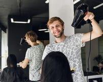 Pelo sonriente profesional del ` s de la mujer del estilista que hace el brushing de sexo masculino con un secador en salón imágenes de archivo libres de regalías